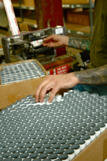 A worker labeling tubes at Portland's Gamblin Artists Colors. Photo by Enid Spitz